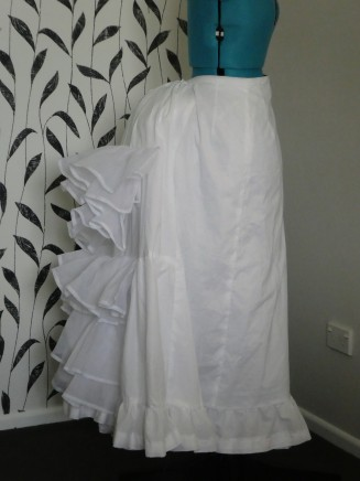 Worn over a bustle cage, pad, and another petticoat